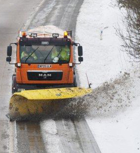 Gritter ploughing a snow covered road